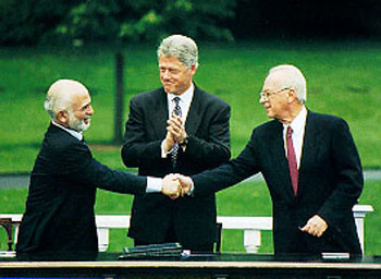A handshake between Hussein I of Jordan and Prime Minister Yitzhak Rabin, accompanied by President Bill Clinton, during the Israel-Jordan peace negotiations.